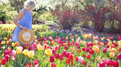 Happy woman walks through flower garden