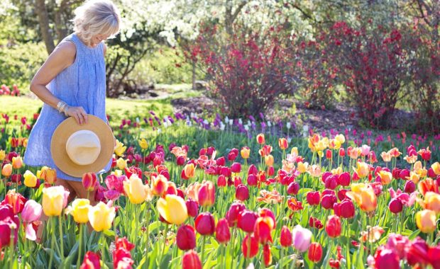 Happy woman walks through flower garden