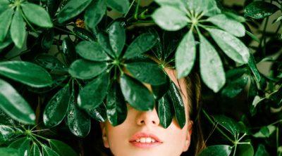 woman hiding amongst garden leaves